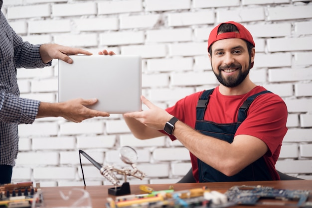 Worker of computer service receives a laptop.