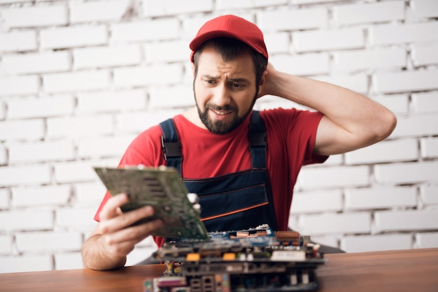 Worker of computer service tired with broken pc.
