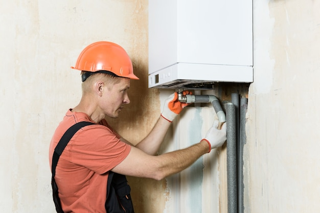 Worker connecting the pipes to a domestic gas boiler