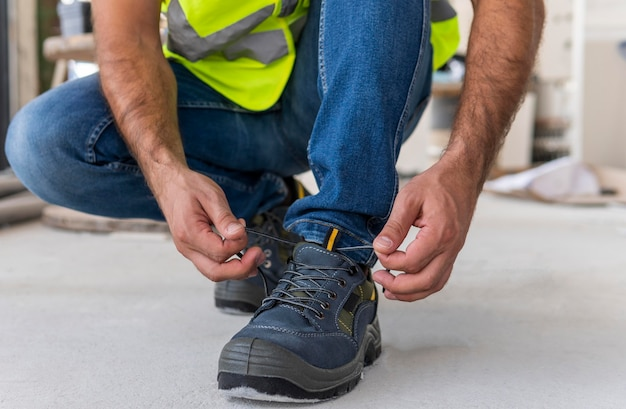 Worker on a construction site tying his shoes