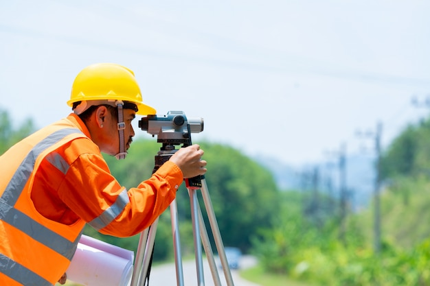 Worker in construction site use theodolite mark at road.
