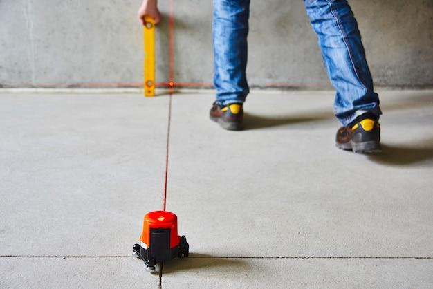 Рабочий контролирует работы стен с помощью лазерного уровня линии. лазерное рулеточное устройство