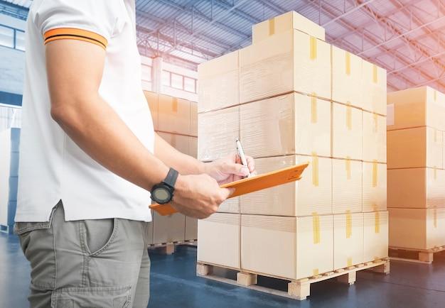 クリップボードを持っている労働者の宅配便業者が保管倉庫の出荷ボックスで在庫管理を行っている