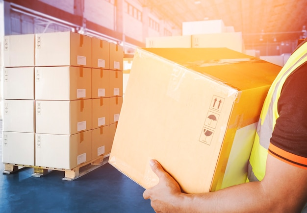 労働者の宅配便は、保管倉庫の出荷サプライチェーンでパッケージボックスを運んでいます