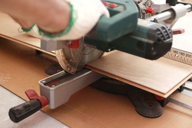 Worker cuts a laminate of a certain length with a saw close up