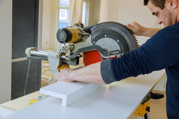 Worker cuts wood baseboard on the power saw