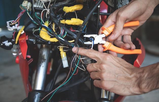 Рабочий, режущий электрические провода плоскогубцами.