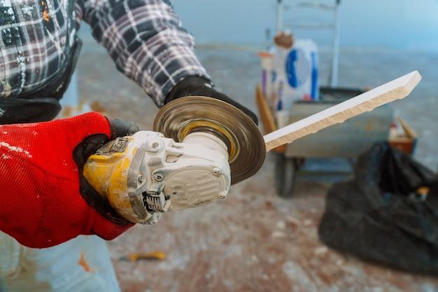 Работник по резке напольной плитки с алмазным электропилом на строительной площадке