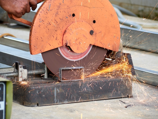 Worker cutting iron with cutting wheels.