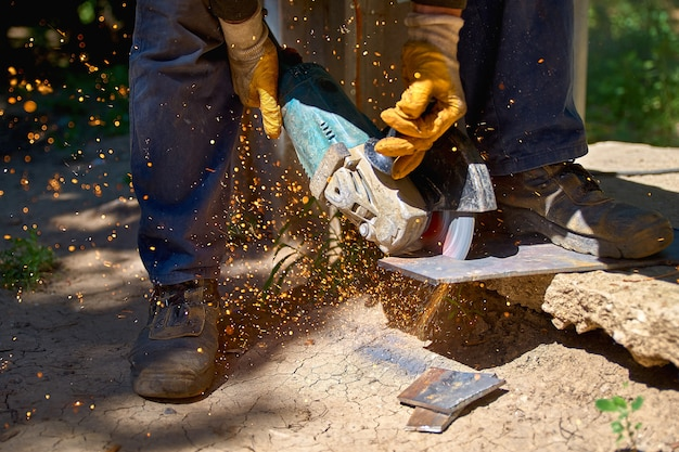 Работник резки металла с измельчителем. искры при шлифовании железа