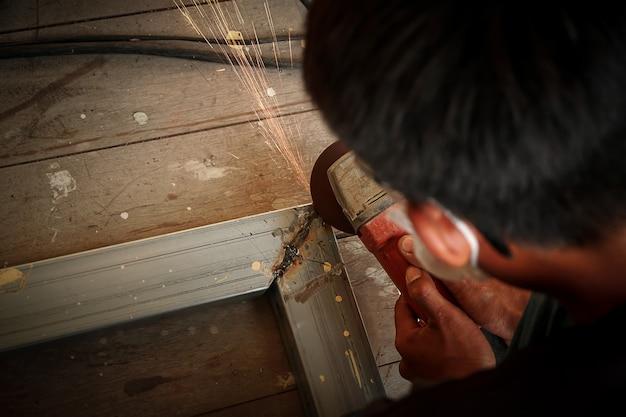 鉄を研削しながらグラインダースパークで金属を切断する作業員