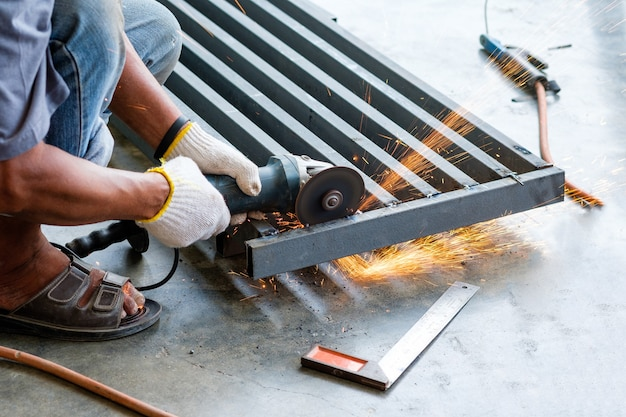 Worker cutting metal with grinder and sparks while grinding steel