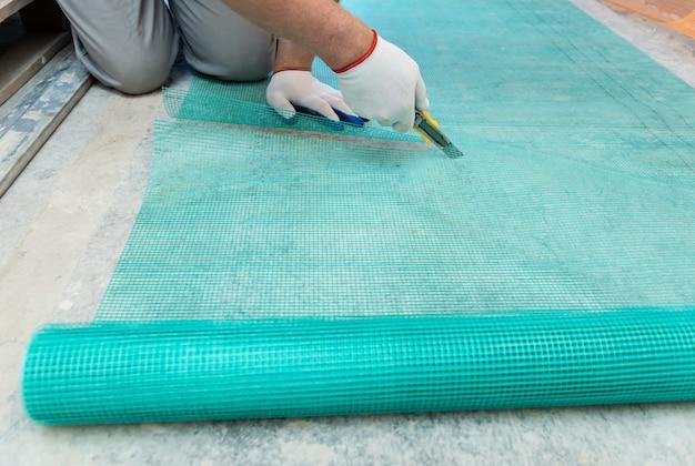 Рабочий отрезает кусок стекловолоконной сетки ножом