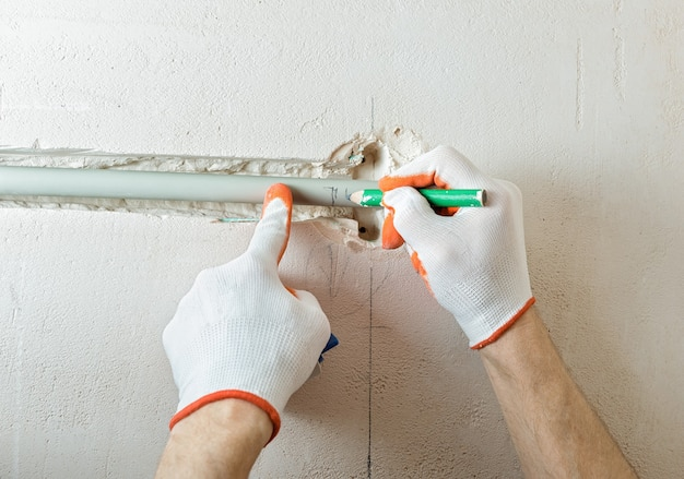 Worker cutting off the part of the insulation with a cutter