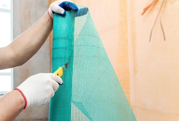 Рабочий отрезает кусок стеклосетки с помощью ножа
