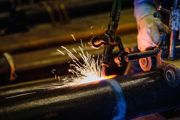 アセチレン溶接トーチと鮮やかな火花を持つワーカー切断鋼管