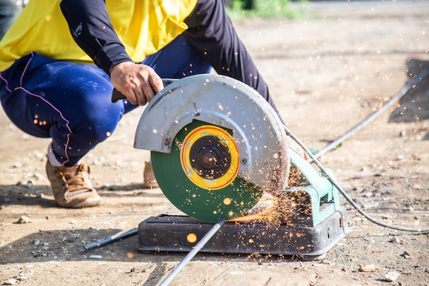 A worker cutting steel with a circular steel cutter. there are sparks from cutting on a construction site.
