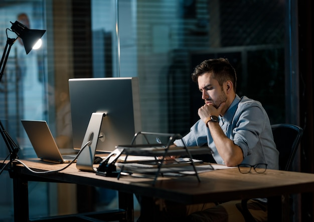 Worker in dark office with papers