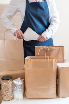 Служба доставки работника упаковочная сумка коробка фартук упаковщик рука почтовая накладная