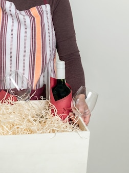 Worker of delivery service packing wine bottle and gifts to box with straw for customer.
