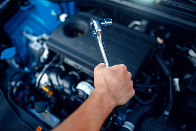 Worker disassembles vehicle engine, car service
