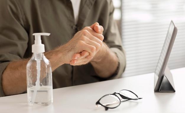 Рабочий, дезинфицирующий руки в офисе