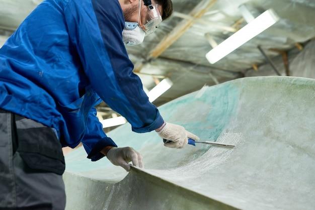 Работник делает ремонт лодок