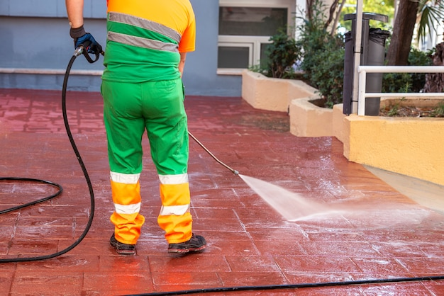 Worker dressed in green work clothes, cleaning the streets for the prevention of covid19 or crown virus with pressurized bleach water gun