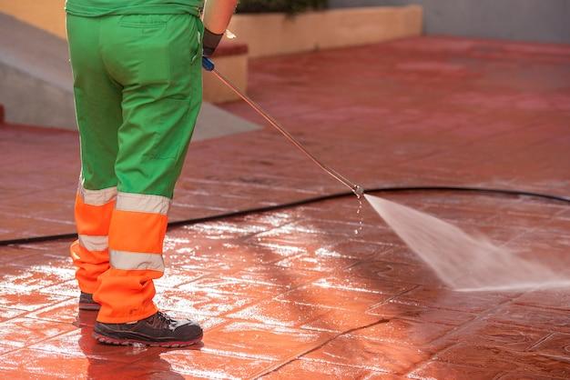 Рабочий, одетый в зеленую рабочую одежду, убирает улицы для предотвращения covid19 или вируса короны с помощью пистолета с отбеливателем под давлением