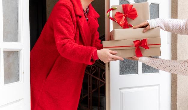 Рабочий, одетый в красное пальто, доставляет подарочные коробки возле белой двери накануне праздников рождества и нового года.