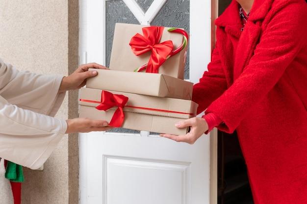 Рабочий в красном пальто доставляет подарочные коробки возле белой двери накануне праздников