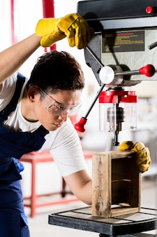 Worker on drilling machine in workshop