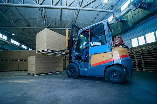 Worker driver of a forklift loader at warehouse of sandwich panels