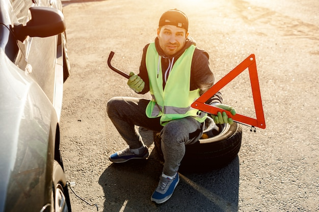 Worker or driver repairing a car. he throws up his hands and does not know what to do. concerned and worried. bad worker. he is dressed in a signal vest.