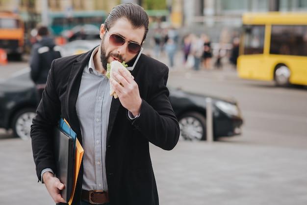 Работник ест, пьет кофе, разговаривает по телефону, одновременно. бизнесмен делает несколько задач. многозадачность делового человека.