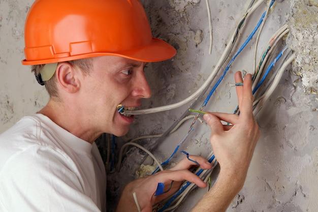 Работник электрика зубы сжимает оборванные провода