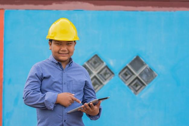 タブレット技術を使用して仕事で幸せな労働者エンジニアの笑顔