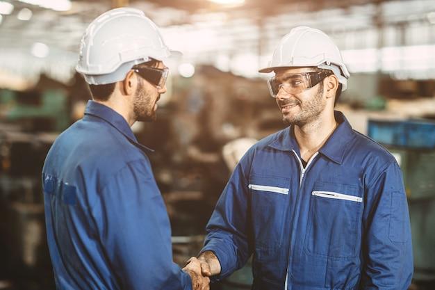 工場労働者のバックグラウンドで行われる取引の仕事を終えてのハンドシェイクを笑顔の労働者エンジニアチーム。