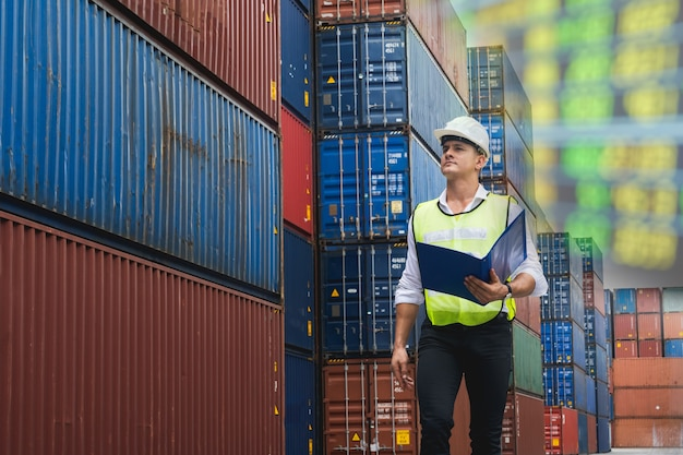 Worker engineer walking to checking the containers box from cargo ship for export and import