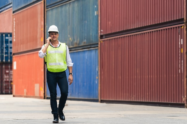 Рабочий-инженер идет к проверке коробки контейнеров с грузового судна для экспорта и импорта