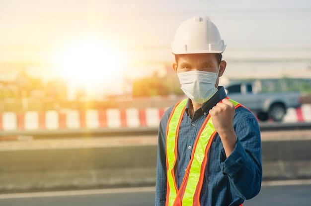 Рабочий инженер носит маску защиты от коронавируса covid19, работая на открытом воздухе на дорожном фоне