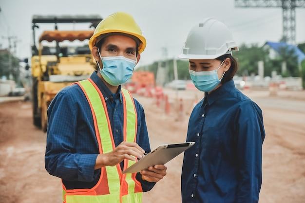 작업자 엔지니어는 사이트 도로 공사에 태블릿으로 작업하는 마스크를 착용
