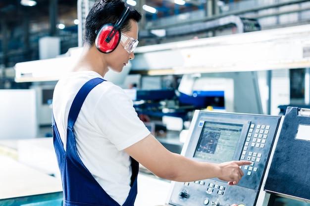 生産を開始するために工場フロアのcncマシンにデータを入力する労働者