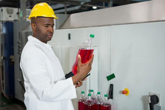 Worker examining bottles in juice factory