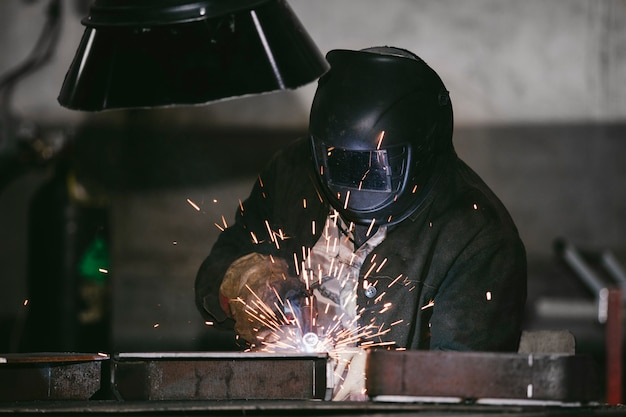 Worker at the factory in the helmet is of iron in the welding process bright sparks
