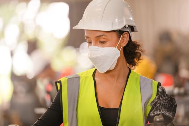 작업자 공장 사람들이 얼굴 마스크와 안전 복을 입고. 공장에서 일하는 여성.