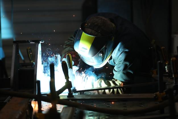 Worker in a factory welding iron