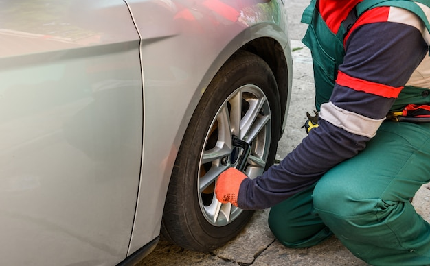 Worker fixing car wheel with spanner close up