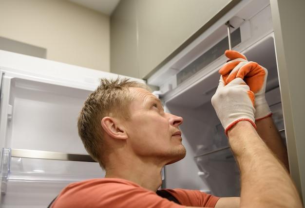 Рабочий, закрепляющий встроенный холодильник на кухонной мебели