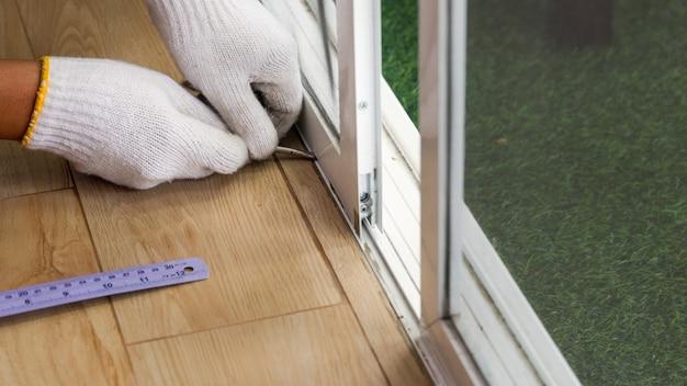 Рабочий, ремонтирующий раздвижную дверь, которая залипает